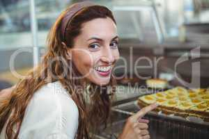 Pretty brunette pointing at pastries through the glass