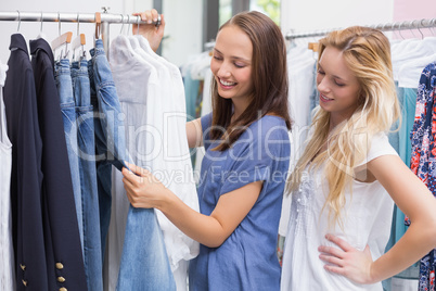 Happy friends browsing in the clothes rack