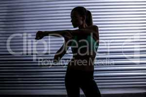 Muscular woman stretching in shadow room