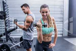 A muscular couple lifting dumbbells