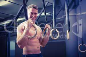 Portrait of smiling muscular man doing ring gymnastics