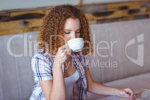 Pretty curly hair girl enjoying a cup of coffee