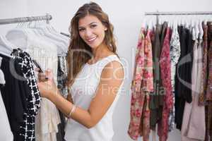 Portrait of smiling woman taking a photo of price tag