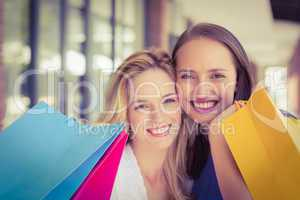 Happy friends holding shopping bags