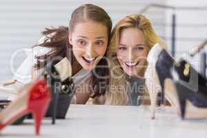 Two excited women looking at heel shoes