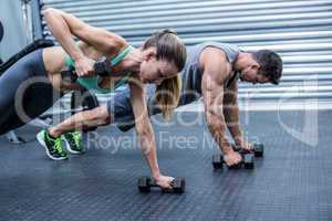 Muscular couple doing plank exercise together