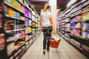 Photo of a woman walking with his trolley on aisle on selective