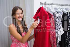 Portrait of smiling woman holding price tag and looking at camer