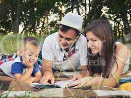 Parents with a child reading a book outdoors