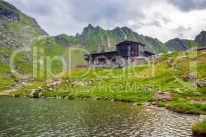 Idyllic view with typical lodge on Balea Lake shore in Fagaras M