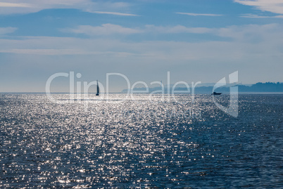 Sailboat and power boat on reflective water
