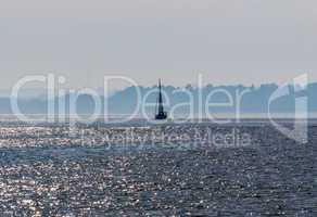 Sailboat on water against hazy shoreline