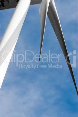 Portion of white wind turbine blades and pylon