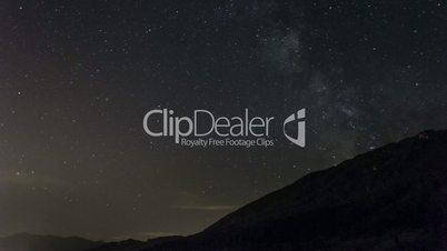 stars moving in night sky over mountain ridge
