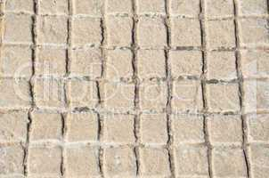 Old floor tiles small beige stone pavement