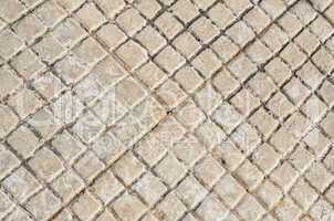 Old floor tiles small beige stone pavement in brace