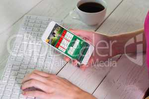 Composite image of woman using smartphone at work