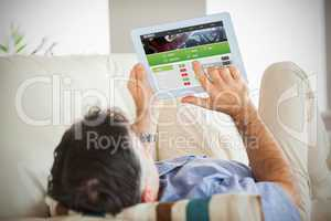 Composite image of man laying on sofa using a tablet pc