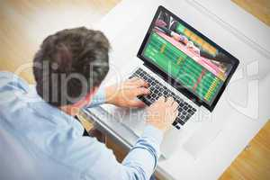 Composite image of man using laptop