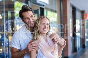 Smiling man embracing his girlfriend and pointing far away