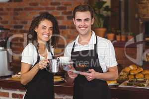 Waiter and waitress smiling at camera