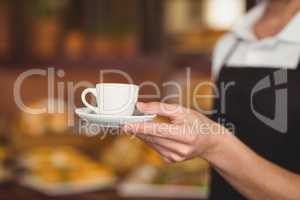 Barista offering cup of coffee
