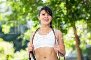 Smiling athletic woman with skipping rope