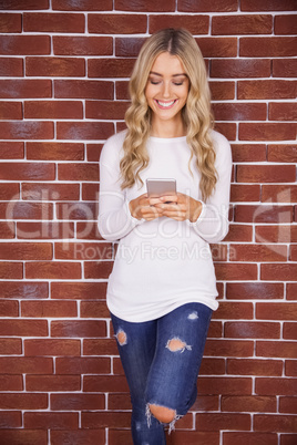 Stylish blonde woman smiling and using smartphone