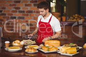 Handsome waiter about to pick a roll