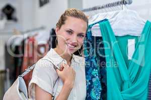Smiling woman standing next to clothes rail