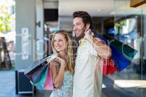Smiling couple with shopping bags looking far away