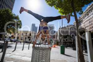 Athletic woman performing handstand and doing split on bin