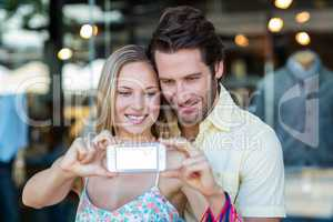 Smiling couple with shopping bags taking selfies