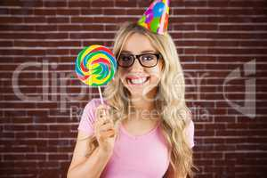 Portrait of a hipster with a party hat holding a lollipop