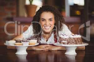 Waitress bending over chocolate cake and cupcakes