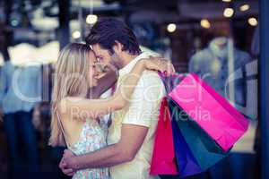 Smiling couple with shopping bags hugging closely