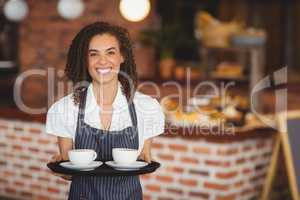 Smiling barista holding a tray of coffee cups