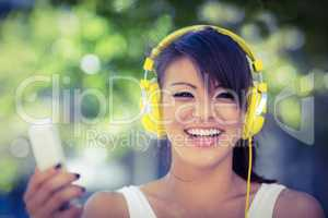 Portrait of smiling athletic woman wearing yellow headphones and