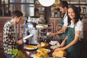 Smiling waiters serving a client
