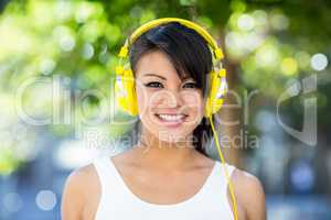Portrait of smiling athletic woman wearing yellow headphones