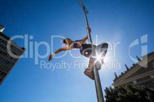 Athletic woman hanging on street sign