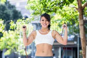 Portrait of smiling athletic woman skipping