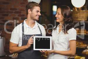 Smiling co-workers showing a tablet