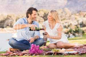 Cute couple on date pouring red wine
