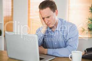 Fearful businessman looking at his laptop