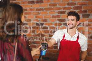 Smiling waiter handing a pin terminal