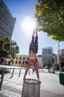 Athletic woman performing handstand on bin