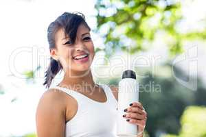 Portrait of smiling athletic woman holding water bottle and look