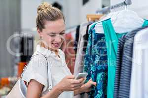 Smiling woman using smartphone while browsing clothes
