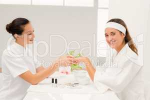 Portrait beautiful woman with beautician applying nail varnish t